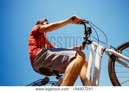 young man ride a bicycle from below shot summer day real people concept