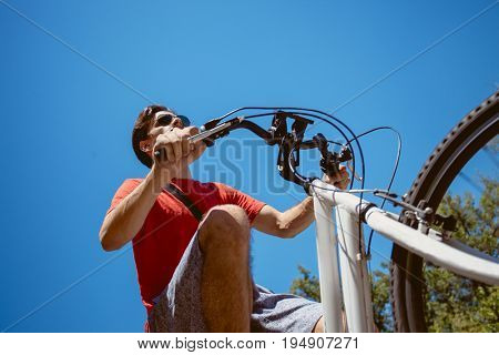 young man with sunglasses  ride a bicycle from below shot hot summer day real people concept