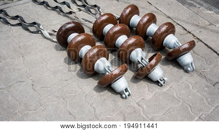 High voltage electricity cable connected with brown ceramic insulators on cement floor.