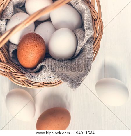 Basket with white and brown natural eggs on white wooden background.