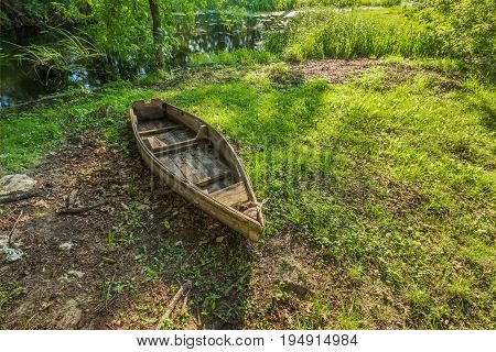 The old forgotten boat does not bank the swamp among the bushes and grass