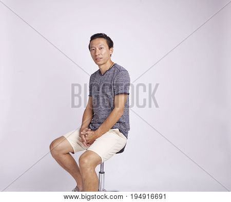 Asian Adult Sitting On Stool Isolated On White