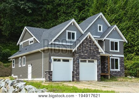 Brand new family house with gravel driveway on country side in British Columbia Canada. Brand new house with green forest background