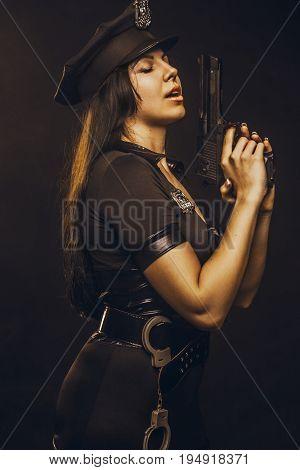 Seductive police woman with gun over dark background