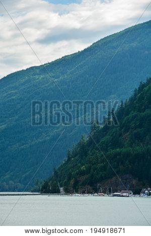 Harrison lake shore view with mountain slop and yachts on the lake