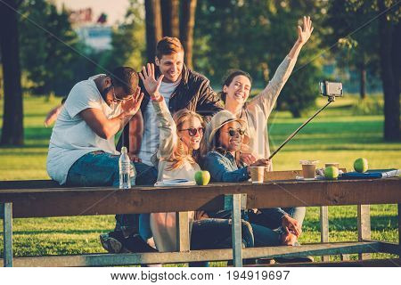 Multi-ethnic group of friends taking a selfie with cellphone.