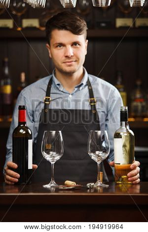 Sommelier with two bottles of red and white wine and wineglasses stands behind the bar. Bartender at work. Professional barista in apron