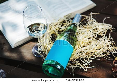 Glasswine with white wine, bottle on sawdust near big open book, romantic background with expensive alcoholic drink