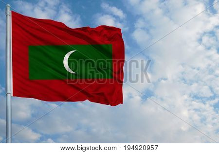 National flag of Maldives on a flagpole in front of blue sky. poster