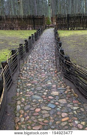 Fence and stone way in Belovezhskaya Puscha in spring