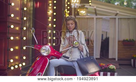 Portrait of young attractive woman sitting on the red scooter. She is searching something in smartphone