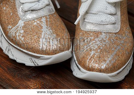 Pair of beige new female sneakers on wooden background closeup