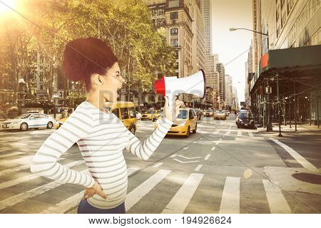 Carefree young woman shouting with megaphone  against new york street