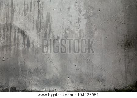 The texture of the grey cement wall with dirty stains and cracks. Plaster cracked from exposure to water.