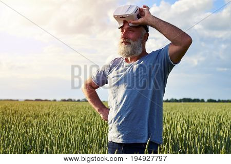 Side view of handsome elderly male putting off 3D glasses on field of weed, hand on hip, mid shot