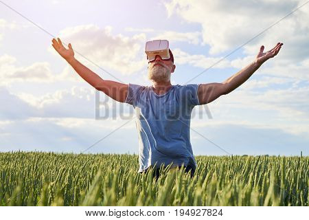 Elderly bearded male rising hands up to the sky, having good shape and posture, standing on field of weed, mid shot