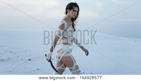 Girl in desert in image of Egyptian mummy with knife in her hand. She goes all wrapped in bandages and she has hieroglyphics on her body..