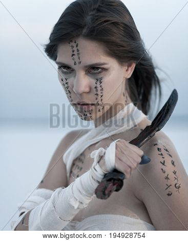 Girl portrait in desert in image of Egyptian mummy with knife in her hand. She all wrapped in bandages and she has hieroglyphics on her body.