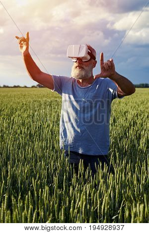 Low angle of elderly bearded man in 3D glasses, Using new technology. Male on the field pointing on something