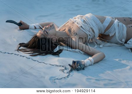 Girl in image of Egyptian mummy lies on sand with metal chain and knife in her hands. She is wrapped in bandages and she has hieroglyphics on her body.
