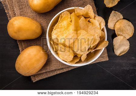 A photo of a bowl of potato chips with potato spuds, shot from above on a burlap and a black texture with a place for text
