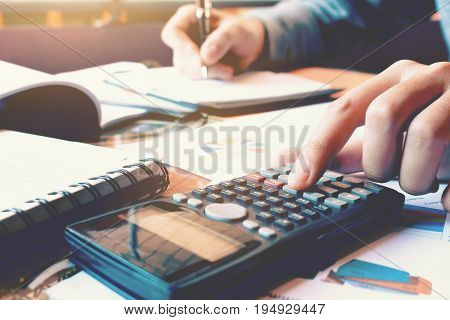 Close up woman hand pressing calculator and doing finance at home office with writing make note report on notebook.
