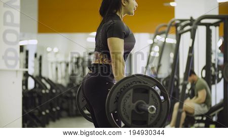 Young woman lifting up and putting down the barbell
