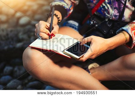 Woman Journalist Reporter With Camera Takes Notes On A Notebook
