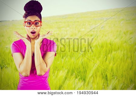 Portrait of surprised young woman standing  against green meadow