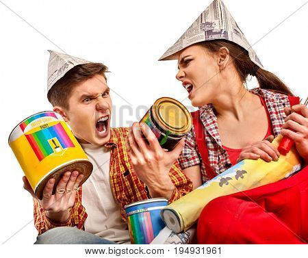 Repair family by aggressive couple building home . Quarrel family because of renovation in new apartment. Mad woman and man in newspaper cap renovation apartment by painting tools.