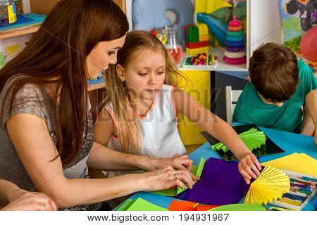 School children with scissors in kids hands cutting paper with teacher for origami in class room. Development and social lerning in kindergarten. Development of fine motor skills in children.