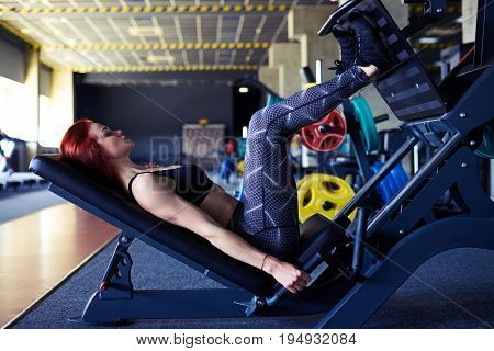 Side view of young woman working her quads at machine press in the gym