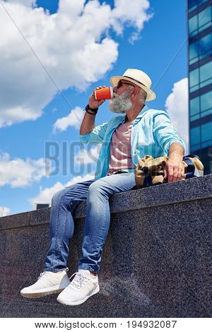 Side view of bearded man sitting and drinking coffee outdoors surrounded by buildings, having hand on bag, mid shot