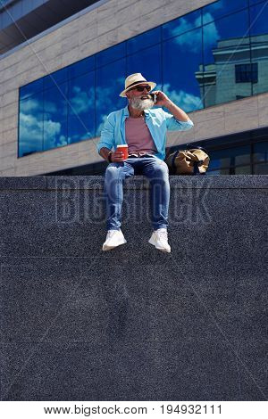 Elderly bearded man sitting talking on phone holding coffee wearing jeans, nice view, mid shot
