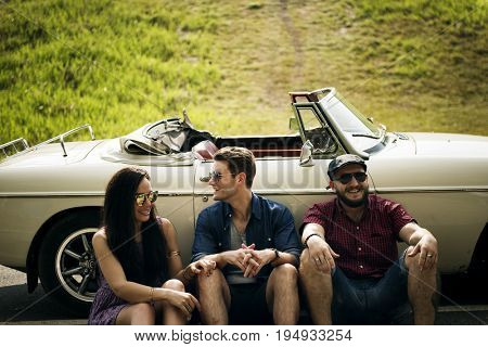 Group of Diverse Friends Sitting on Road by the Car Together