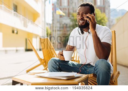 Can you come. Handsome young productive man calling his colleague and setting up a meeting while having a cup of coffee at his favorite place
