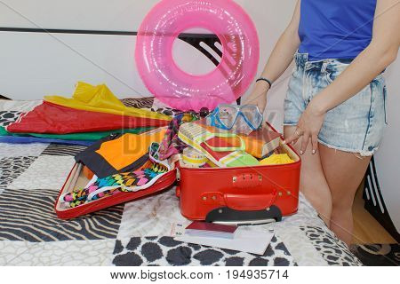 Happy young woman in colorful summer outfit near the red staffed suitcase. Travel concept. Getting ready for travelling to the sea.