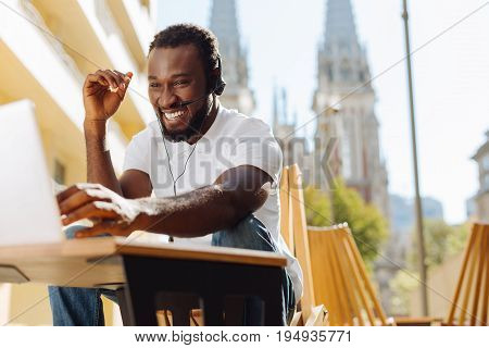 Limitless communication. Handsome dynamic fun man making a video call and talking to his fellow from another country while using his laptop