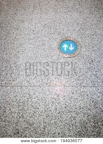 Green arrows sign on granite floor in an airport terminal. Copy-space on the left and below.