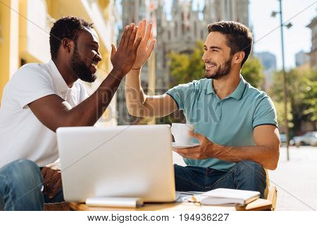 Nice work. Lovely confident inspired man giving his friend a high five while deciding joining him on his new startup and helping him out with some aspects