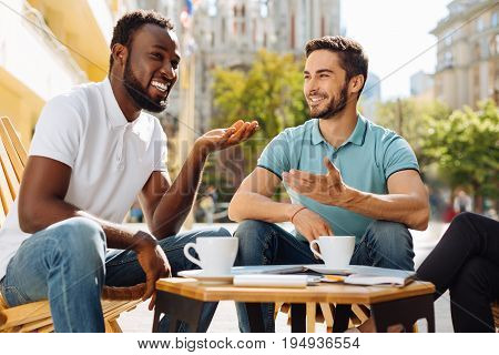 Laughter makes us closer. Bright active enthusiastic man enjoying his time with friends while sitting on a terrace and having a lovely conversation