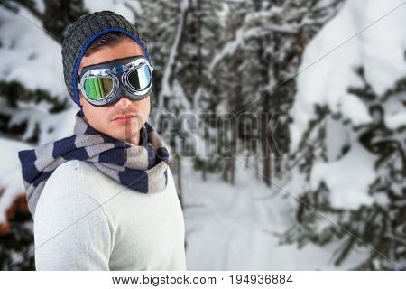 Man wearing aviator goggles against white background against snow covered pine trees on alp mountain slope