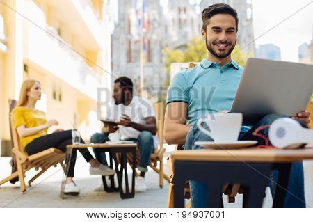 Fresh air everywhere. Hardworking bright organized man visiting his favorite cafe and sitting in a terrace while having a productive day with his project