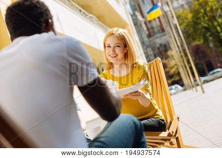 Would you help me. Young independent extraordinary entrepreneur meeting her colleague on a terrace and giving him an assignment while working on some project