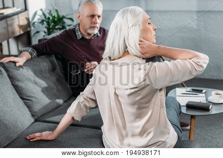 Side View Of Senior Woman Suffering From Strong Neck Ache
