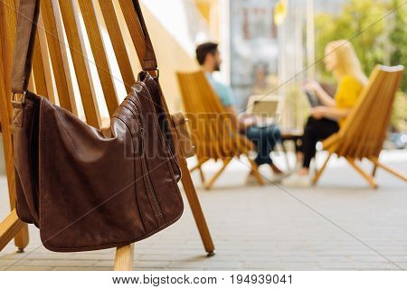 Pleasant place. Industrious charming ambitious people sitting on a terrace and talking to each other while enjoying the day outdoors