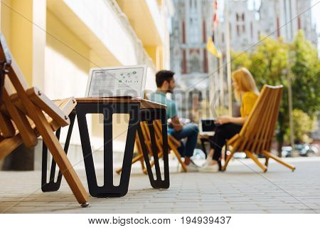 Lunch time errands. Two charismatic competitive open minded fiends sitting on a terrace and discussing details of their project while enjoying their conversation