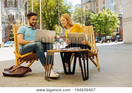 Turn it to me. Cheerful charming easy going man working on something and asking his colleagues taking a look while she sitting next to him