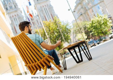 Modern freelance. Progressive smart strategic guy sitting on a terrace and fulfilling his assignments while receiving a message from his employer
