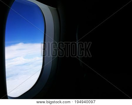 Airplane window view with blue sky; taken on board during light off; with copy space on the right.